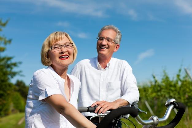 Casal feliz, andar de bicicleta ao ar livre no verão