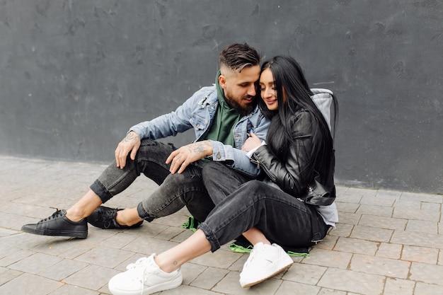 Casal feliz ao ar livre e apaixonado posando perto de um café