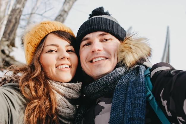 Casal feliz apaixonado fazendo selfie no parque natural da floresta na estação fria.