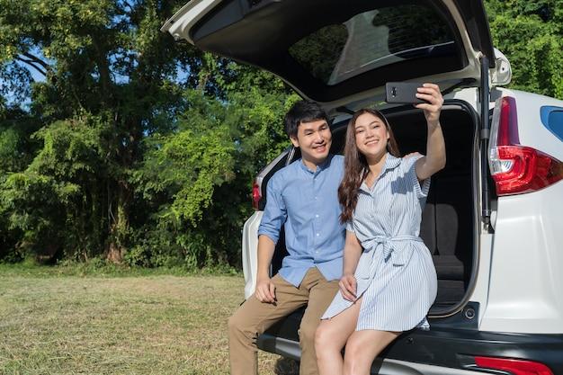 Casal feliz apaixonado sentado e usando o smartphone tirando uma selfie na parte traseira do carro aberto