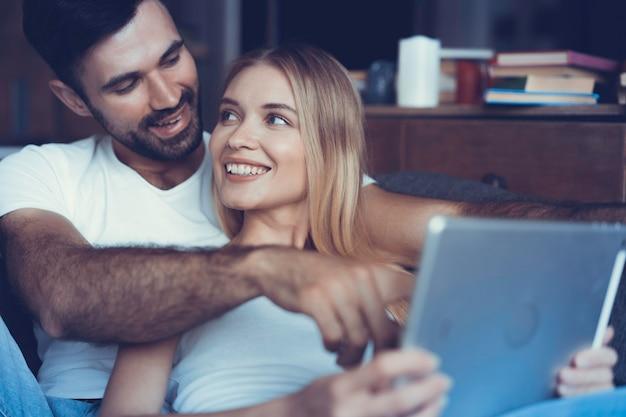 Casal feliz apaixonado surfando no tablet em casa.