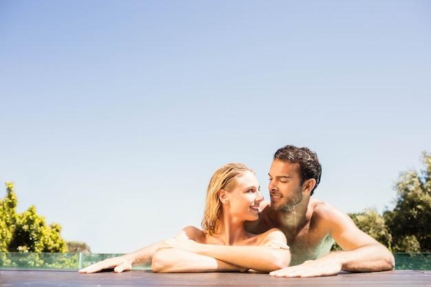 Casal feliz, apoiando-se na borda da piscina em um dia ensolarado