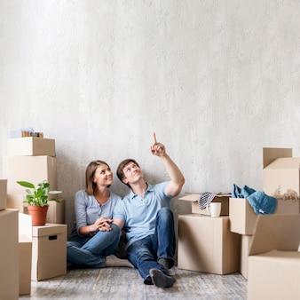 Casal feliz apontando para cima enquanto faz as malas para se mudar