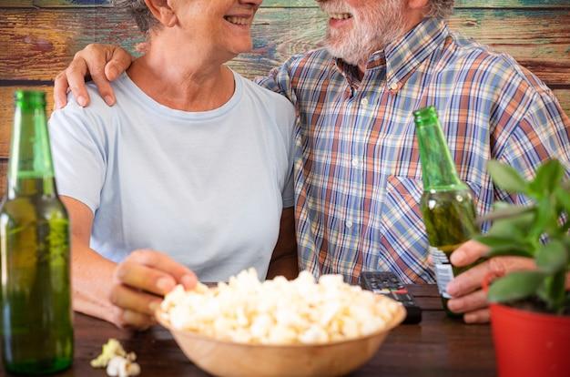 Casal feliz aposentado sentado em um bar com duas garrafas de cerveja e um pouco de pipoca