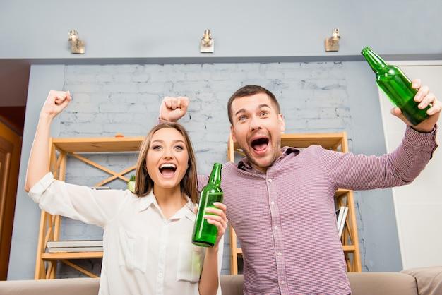 Casal feliz assistindo futebol com cerveja e triunfando com as mãos levantadas