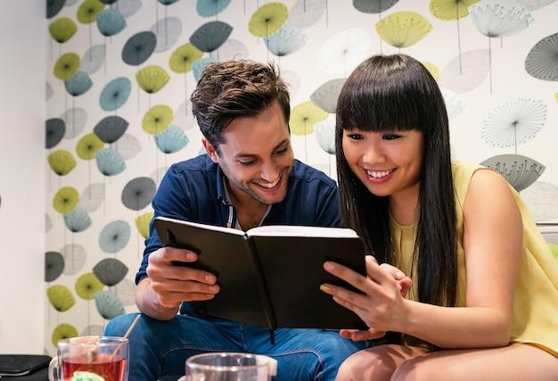 Casal feliz assistindo mídia social em um notebook no bar. eles estão estudando ou trabalhando.