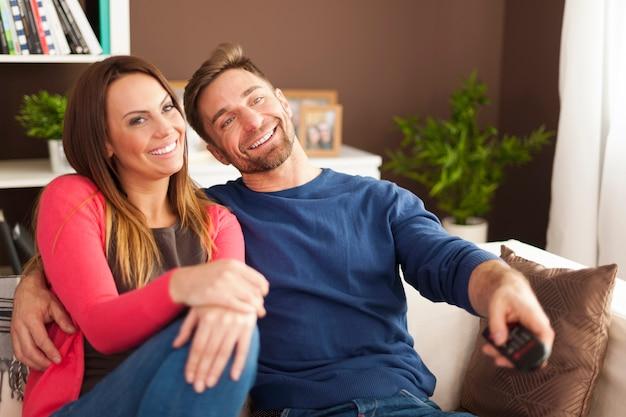 Casal feliz assistindo tv em casa