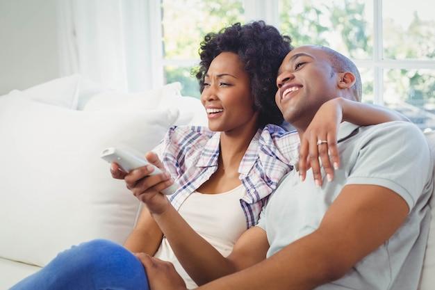 Casal feliz assistindo tv no sofá