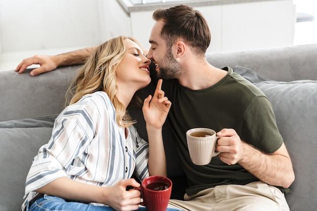 Casal feliz assistindo tv sentado no sofá da sala, bebendo chá, se beijando