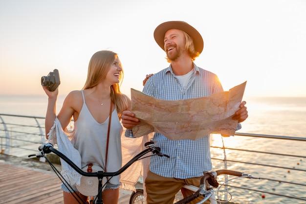 Casal feliz atraente viajando no verão em bicicletas, homem e mulher com cabelo loiro boho hipster estilo moda se divertindo juntos, olhando no mapa turístico tirando fotos na câmera