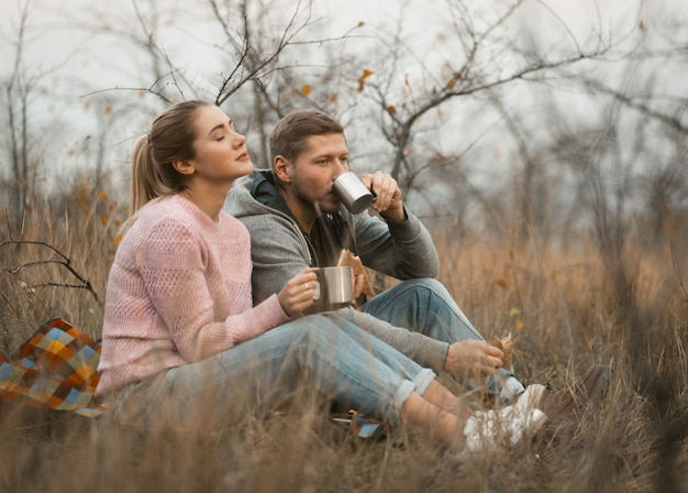 Casal feliz bebe café olhando o pôr do sol ao ar livre