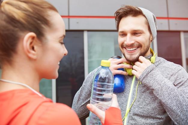 Casal feliz bebendo água após o exercício