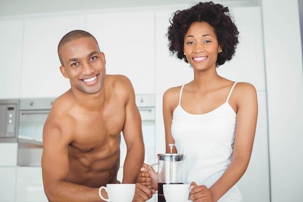 Casal feliz bebendo café na cozinha em casa
