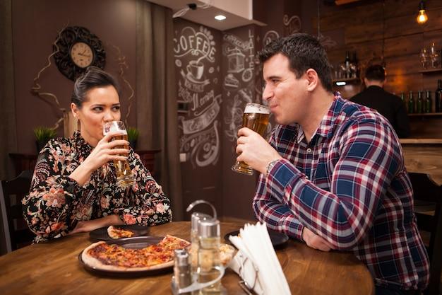 Casal feliz bebendo cerveja e comendo pizza. tempo casual.