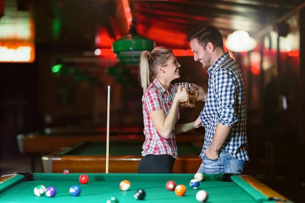 Casal feliz bebendo cerveja e jogando sinuca em um encontro