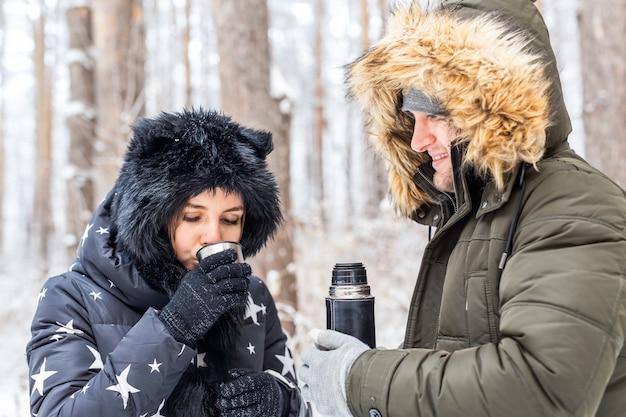 Casal feliz bebendo chá quente na floresta de inverno