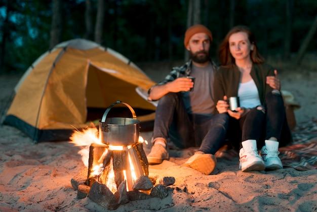 Casal feliz bebendo juntos pela fogueira