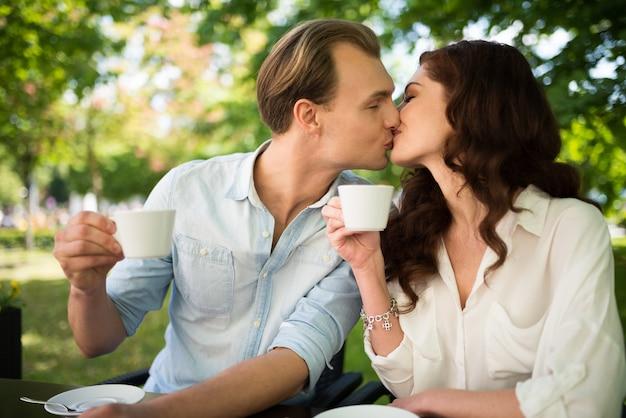 Casal feliz bebendo um cappuccino e beijando enquanto está sentado ao ar livre