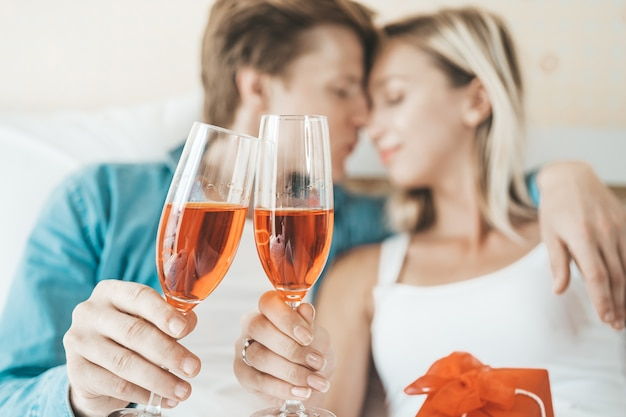 Casal feliz bebendo vinho no quarto