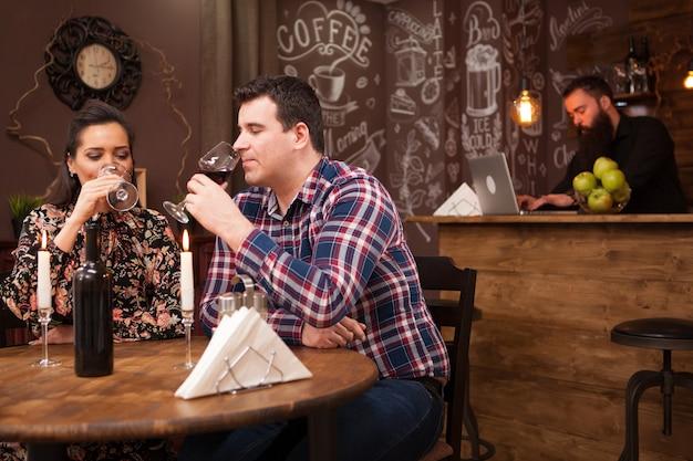 Casal feliz bebendo vinho quando encontro no restaurante. casal bonito.