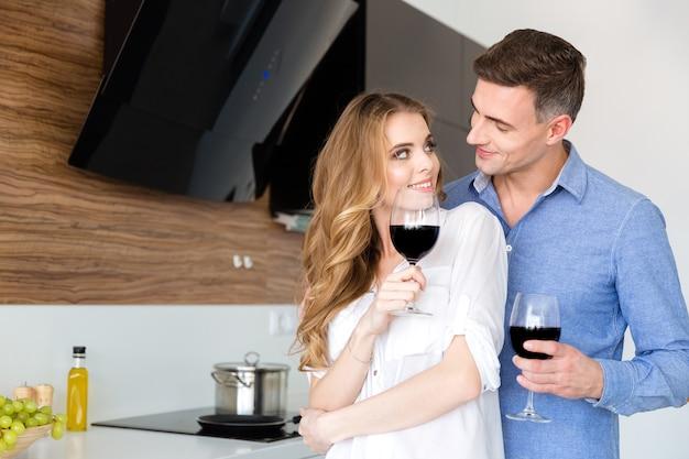 Casal feliz bebendo vinho tinto e flertando na cozinha de casa