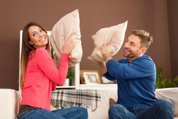 Casal feliz brigando de travesseiro na sala de estar