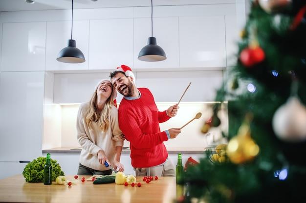 Casal feliz brincalhão com chapéus de papai noel na cabeça em pé na cozinha e preparando o jantar para a véspera de ano novo