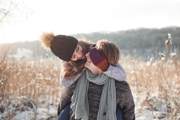 Casal feliz brincalhão juntos durante férias de férias de inverno lá fora no parque de neve