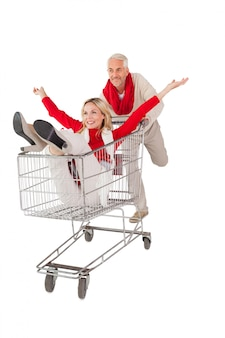 Casal feliz brincando no carrinho de compras