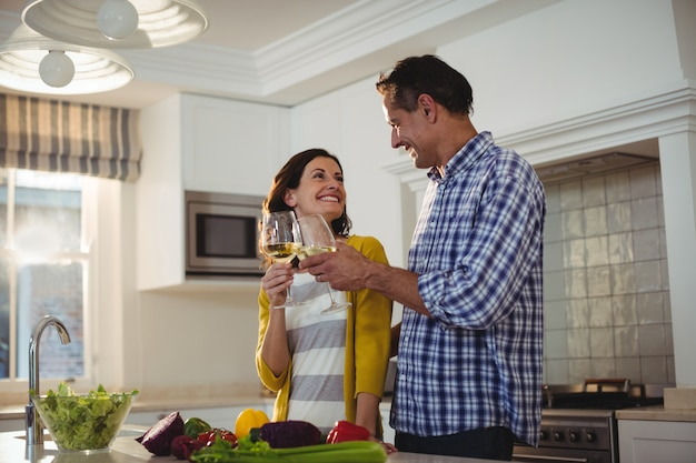 Casal feliz brindando com taças de vinho na cozinha