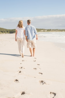 Casal feliz caminhando de mãos dadas