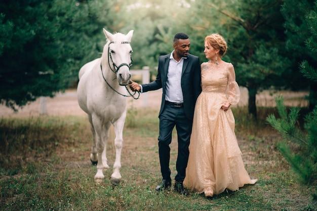 Casal feliz caminhando juntos em um rancho com cavalos ao pôr do sol