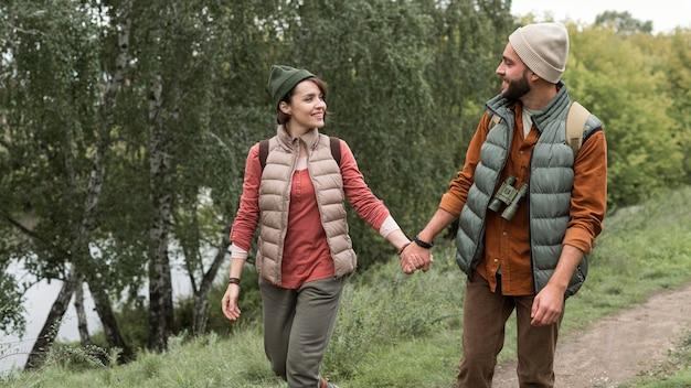 Casal feliz caminhando por uma trilha na natureza