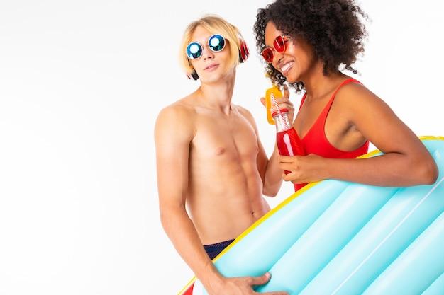 Casal feliz cara europeu e garota africana em trajes de banho com óculos olha de soslaio na parede branca