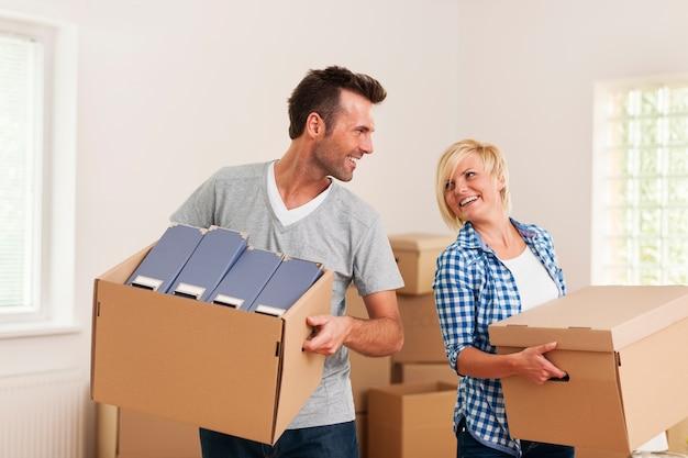 Casal feliz carregando caixas de papelão em apartamento novo