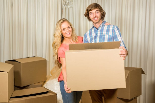 Casal feliz carregando uma caixa em movimento em sua nova casa