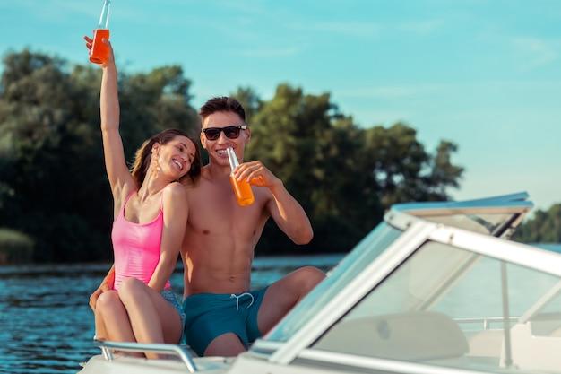 Casal feliz. casal jovem moderno curtindo a companhia um do outro em um iate, se divertindo com bom tempo
