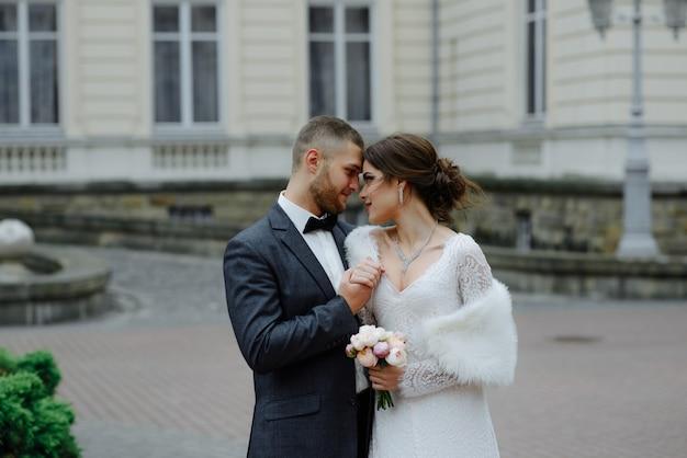 Casal feliz casamento de luxo beijando e abraçando perto retrô com carro buquê no outono