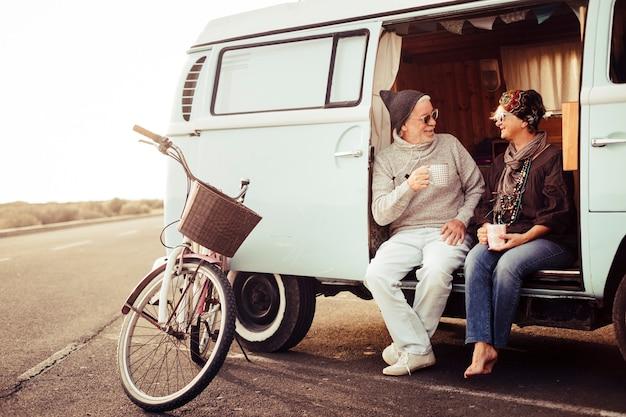 Casal feliz caucasiano com idade avançada senta-se em uma van vintage, bebendo chá e aproveitando a atividade de lazer ao ar livre durante as férias de viagem - bicicleta estacionada perto do veículo