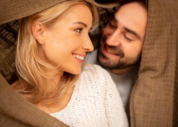 Casal feliz coberto com cobertor closeup