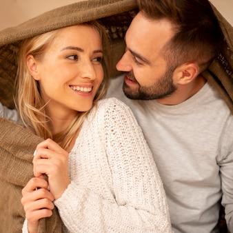 Casal feliz coberto com cobertor