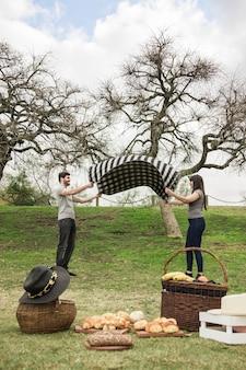 Casal feliz colocando cobertor xadrez no piquenique no parque