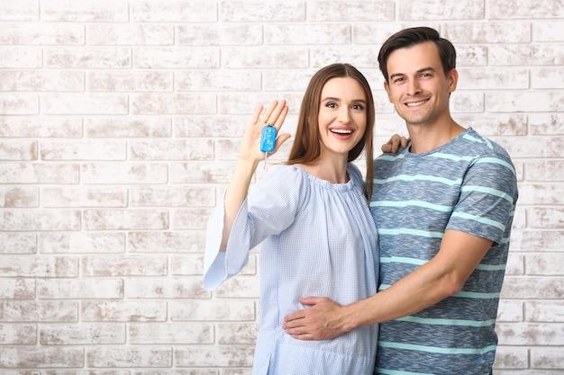 Casal feliz com a chave de seu novo carro na parede de tijolos