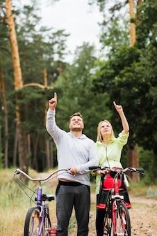 Casal feliz com bicicletas apontando para cima