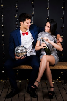 Casal feliz com bola de discoteca e uma garrafa de champanhe