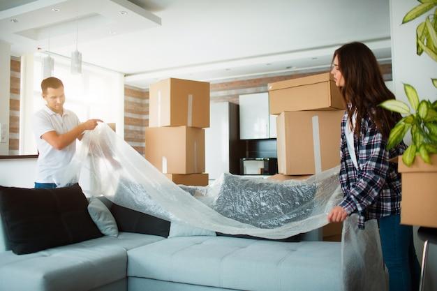 Casal feliz com caixas de papelão em casa nova no dia da mudança.