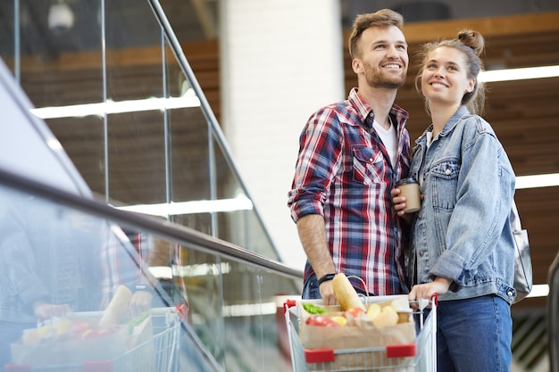 Casal feliz com carrinho de compras