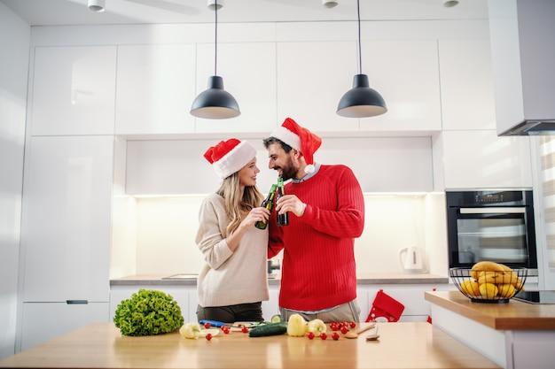 Casal feliz com chapéus de papai noel na cabeça brindando com cerveja em pé na cozinha na véspera de natal