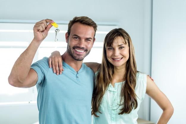 Casal feliz com chave na casa nova