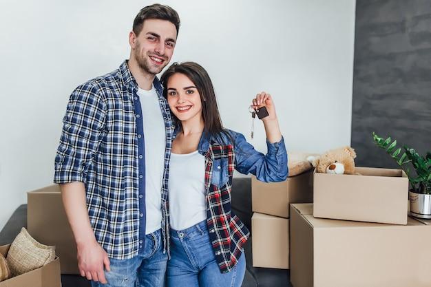 Casal feliz com chaves de novos apartamentos